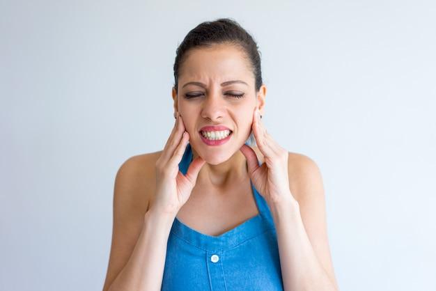 Jovem mulher irritada que sofre da dor de dente e que toca na maxila.