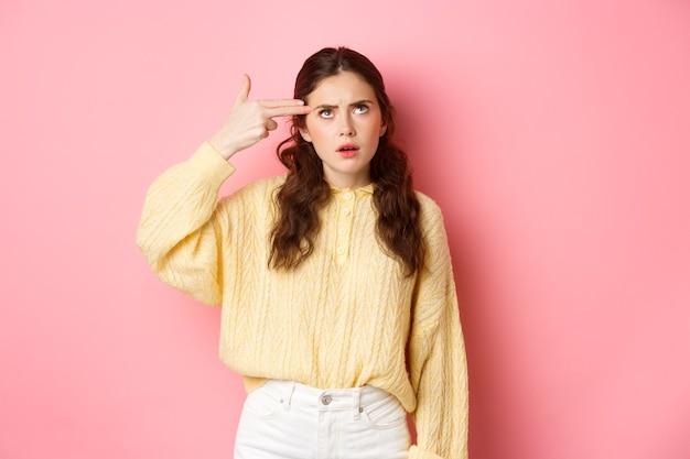 Jovem mulher irritada revirou os olhos e fez um gesto de atirar com o dedo de algo manco, de pé incomodado contra a parede rosa.
