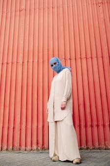 Jovem mulher islâmica casual em um hijab e traje casual em pé perto de uma parede vermelha em ambiente urbano