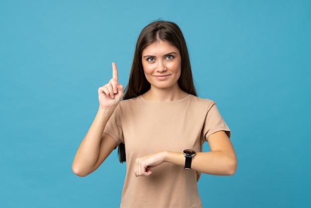 Jovem mulher isolada azul olhando para o relógio de mão