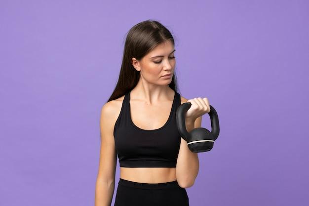 Jovem mulher isolada fazendo levantamento de peso com kettlebell