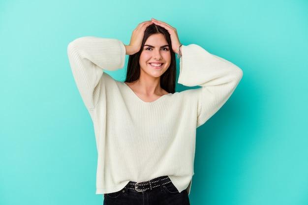 Jovem mulher isolada na parede azul ri com alegria, mantendo as mãos na cabeça. conceito de felicidade