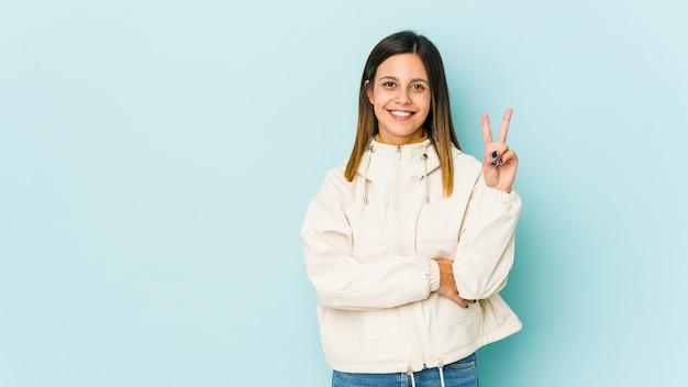 Jovem mulher isolada no número mostrando azul dois com dedos.