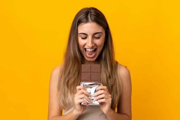 Jovem mulher isolada parede amarela comendo uma tablete de chocolate
