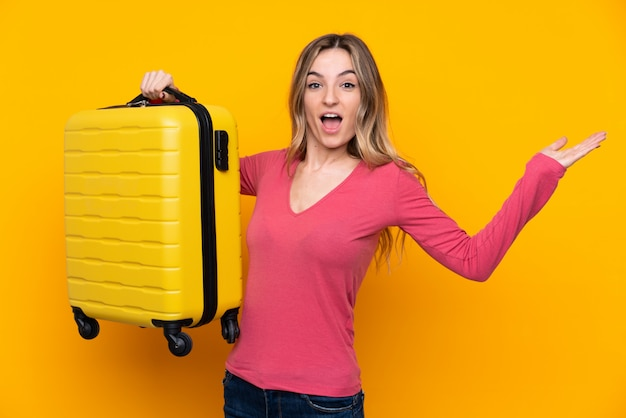 Jovem mulher isolada parede amarela em férias com mala de viagem e surpreso