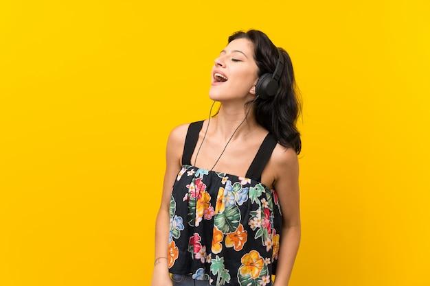 Jovem mulher isolada parede amarela, ouvindo música com fones de ouvido