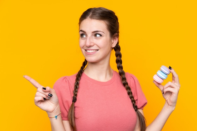 Jovem mulher isolada parede amarela segurando macarons franceses coloridos e apontando o lado