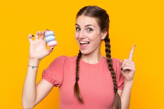 Jovem mulher isolada parede amarela segurando macarons franceses coloridos e apontando uma ótima idéia