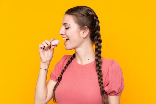 Jovem mulher isolada parede amarela segurando macarons franceses coloridos e comê-lo