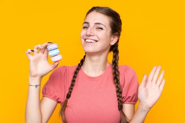 Jovem mulher isolada parede amarela segurando macarons franceses coloridos e saudando