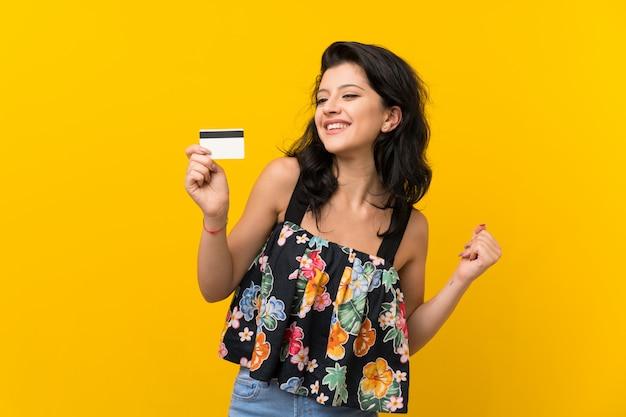 Jovem mulher isolada parede amarela segurando um cartão de crédito