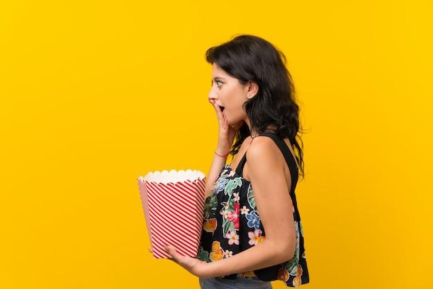 Jovem mulher isolada parede amarela segurando uma tigela de pipocas