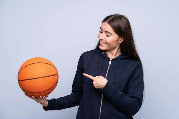 Jovem mulher isolada parede azul com bola de basquete e apontando-o