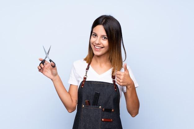 Jovem mulher isolada parede azul com cabeleireiro ou barbeiro vestido com o polegar para cima