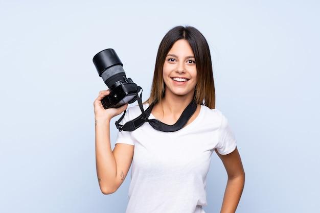 Jovem mulher isolada parede azul com uma câmera profissional