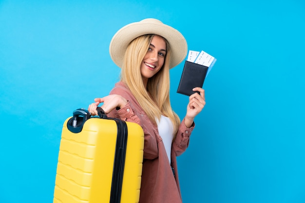Jovem mulher isolada parede azul em férias com mala e passaporte