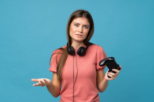Jovem mulher isolada parede azul jogando em videogame