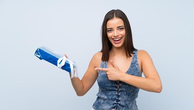 Jovem mulher isolada parede azul segurando a caixa de presente