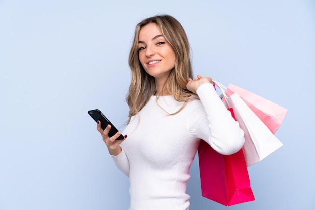 Jovem mulher isolada parede azul segurando sacolas de compras e escrever uma mensagem com o celular para um amigo