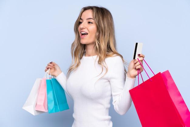 Jovem mulher isolada parede azul segurando sacolas de compras e um cartão de crédito