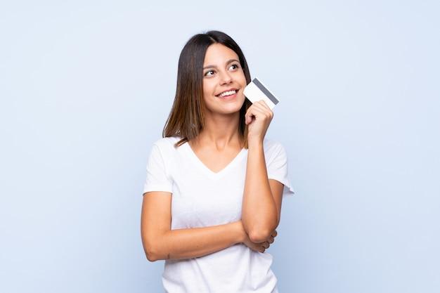 Jovem mulher isolada parede azul segurando um cartão de crédito
