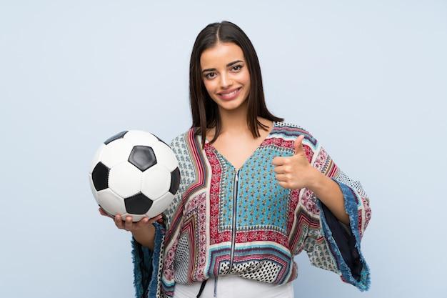 Jovem mulher isolada parede azul segurando uma bola de futebol