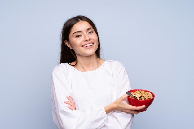 Jovem mulher isolada parede azul segurando uma tigela de cereais