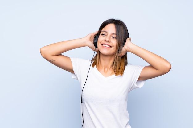 Jovem mulher isolada parede azul usando o celular com fones de ouvido