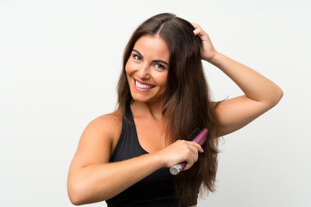 Jovem mulher isolada parede branca com pente de cabelo