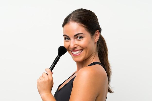 Jovem mulher isolada parede branca com pincel de maquiagem