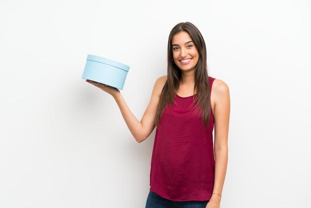 Jovem mulher isolada parede branca segurando a caixa de presente