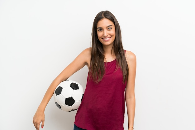 Jovem mulher isolada parede branca segurando uma bola de futebol