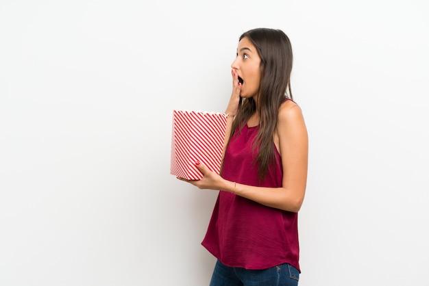 Jovem mulher isolada parede branca segurando uma tigela de pipocas