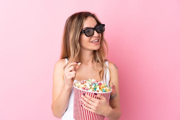 Jovem mulher isolada parede rosa com óculos 3d e segurando um grande balde de pipocas