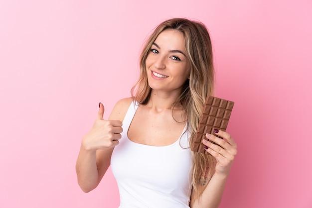 Jovem mulher isolada parede rosa tomando uma tablete de chocolate e com o polegar