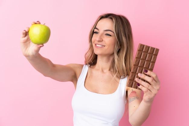 Jovem mulher isolada parede rosa tomando uma tablete de chocolate em uma mão e uma maçã na outra