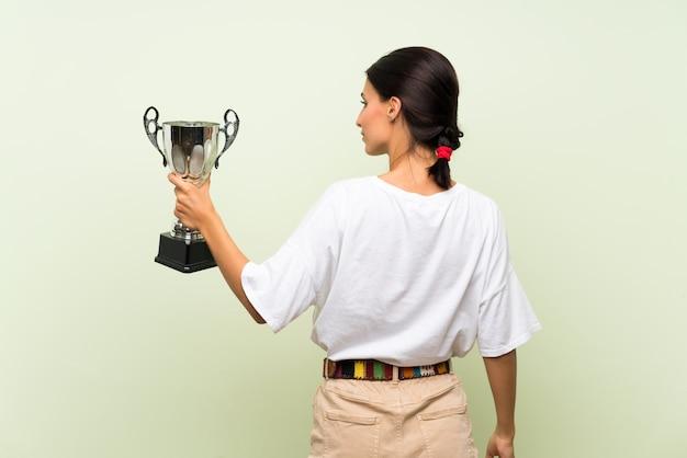 Jovem mulher isolada parede verde segurando um troféu
