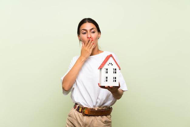 Jovem mulher isolada parede verde segurando uma casinha