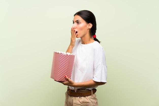 Jovem mulher isolada parede verde segurando uma tigela de pipocas