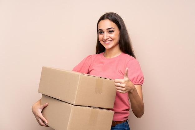 Jovem mulher isolada segurando uma caixa para movê-lo para outro site com o polegar para cima