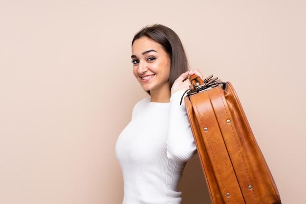 Jovem mulher isolada segurando uma maleta vintage