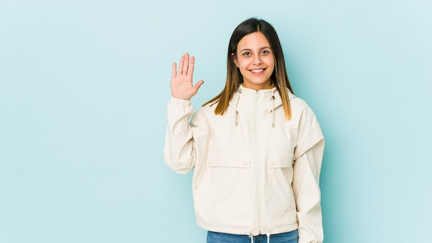 Jovem mulher isolada sobre fundo azul sorrindo alegre mostrando o número cinco com os dedos.