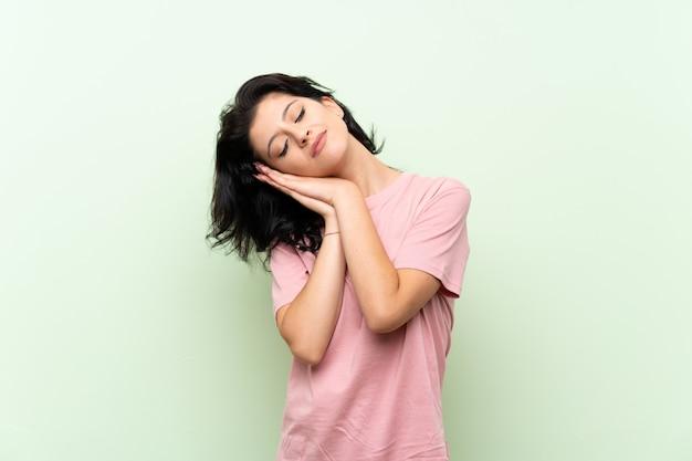Jovem, mulher, isolado, verde, fazer, sono, gesto, em, dorable, expressão