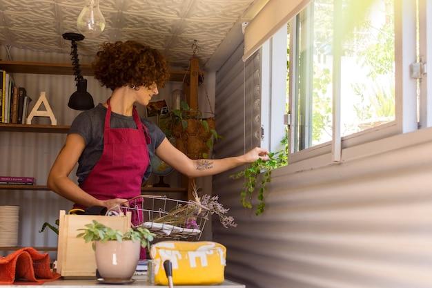 Jovem mulher jardinagem dentro de casa