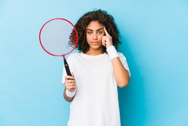 Jovem mulher jogando badminton, apontando o templo com o dedo, pensando, focado em uma tarefa