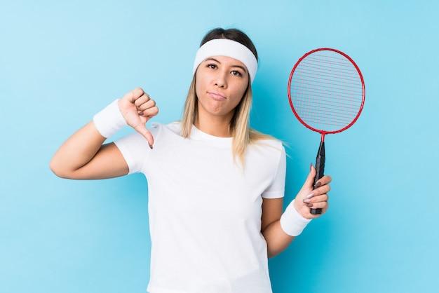 Jovem mulher jogando badminton, mostrando um gesto de antipatia, polegares para baixo. conceito de desacordo.