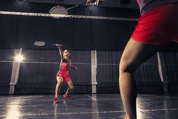 Jovem mulher jogando badminton no ginásio