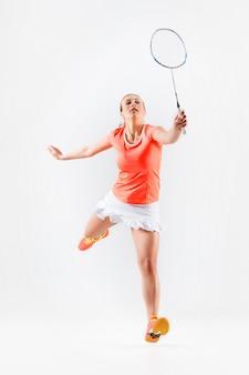 Jovem mulher jogando badminton sobre parede branca