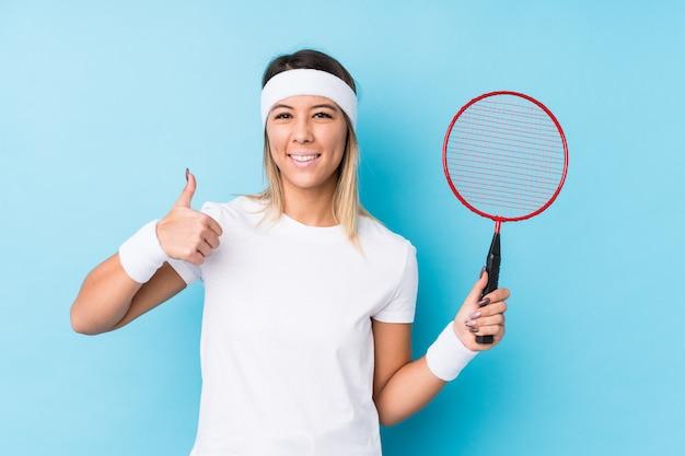 Jovem mulher jogando badminton, sorrindo e levantando o polegar