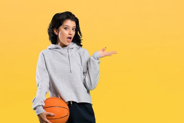 Jovem mulher jogando basquete com expressão facial chocada